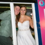 The bride and groom posing in an Ice Scream Social ice cream truck, available for wedding rentals